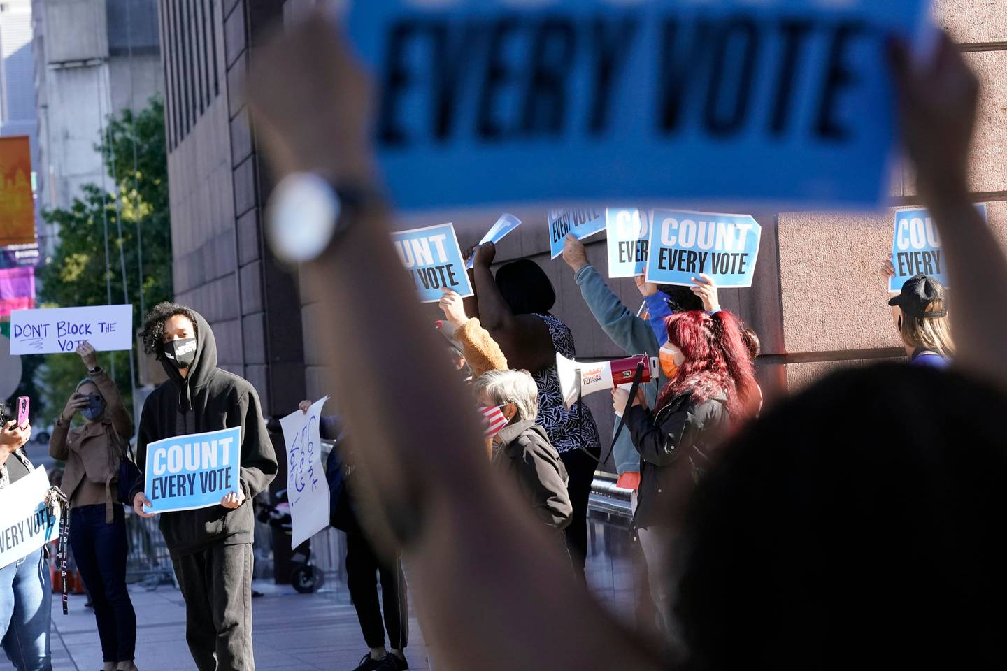 Demonstrators stand across the street from the federal courthouse in Houston, Texas, before a hearing involving drive-thru ballots on November 2. Photo / AP