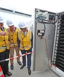 Vector CEO, Simon Mackenzie, project manager Paul Cannin and Minister of Energy & Resources, Hon Simon Bridges inspect the Tesla Powerpack at Vector's Glen Innes substation. Photo / Supplied.