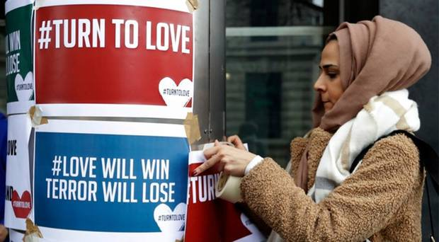 A woman in London puts up a banner in solidarity with the victims. Photo / AP