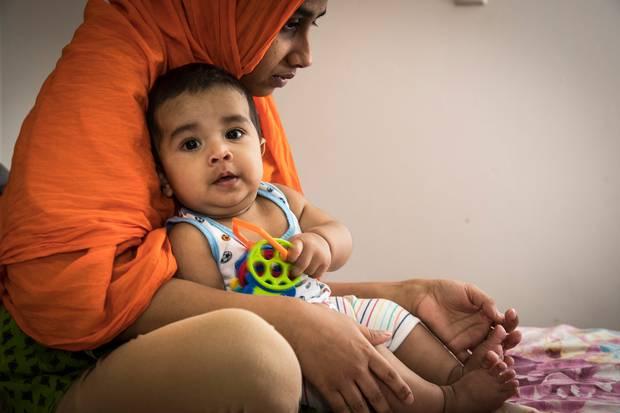 Syed's widow Nishat Abedi holds their son Abdul Fahad Syed. Photo / Michael Craig