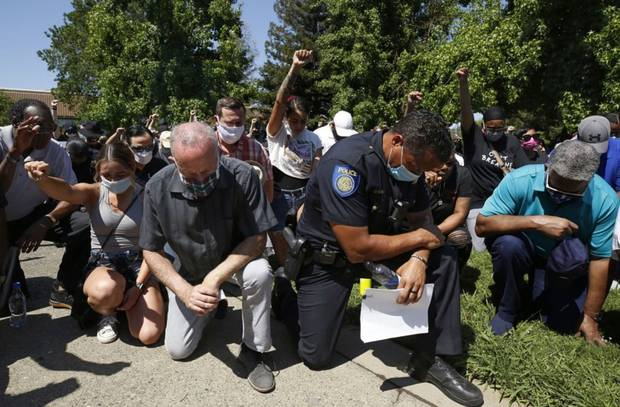 Sacramento Mayor Darrell Steinberg, left, and Sacramento Police Chief Daniel Hahn, right, kneel with others for a moment of silence at a rally in honour of George Floyd. Photo / AP