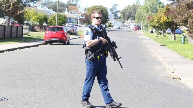 An armed officer at the corner of Kiwi St and Takapu St. Photo / Duncan Brown