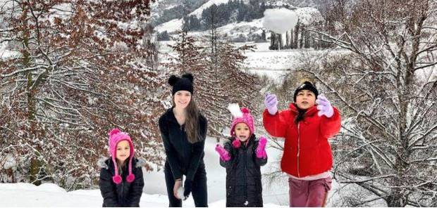 Liz Dotcom plays in the snow with three of Kim's children at the Dotcoms' new home near Queenstown on Thursday. Photo / Daisy Hudson