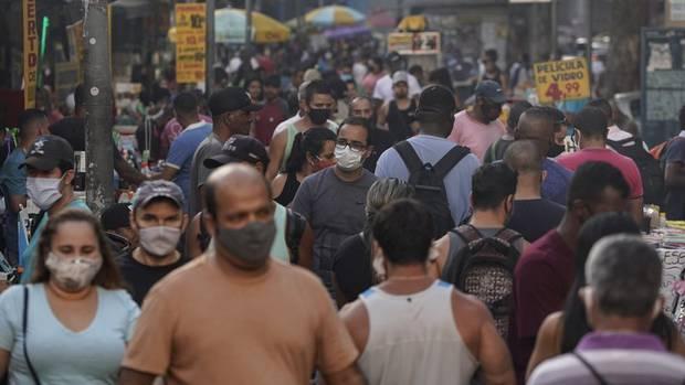 Pedestrians, some wearing protective face masks, walk through a street market in downtown Rio de Janeiro, Brazil. Photo / AP