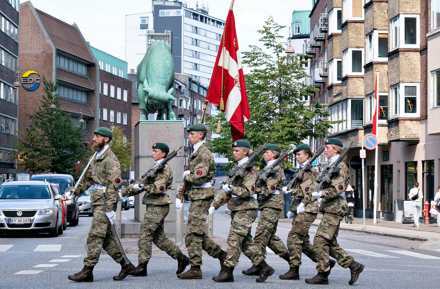 Soldiers march as they carry the Danish flag past the Cimbrer Bull sculpture, during the official Flag Day in honour of Denmark's deployed soldiers through the ages, in Aalborg, Denmark. Photo / AP