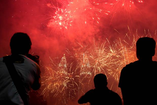 Spectators watch as fireworks explode in front of Malaysia's Petronas Twin Towers. Photo / AP