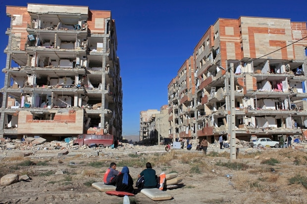 Survivors sit in front of buildings damaged by an earthquake, in Sarpol-e-Zahab. Photo / AP