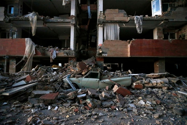 A car lies smashed by debris from the earthquake at Sarpol-e-Zahab yesterday. Photo / ISNA via AP