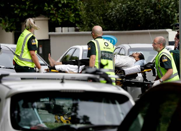Ambulance staff take a man from outside a mosque in central Christchurch. Photo / AP