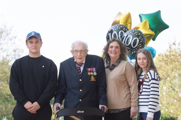 Tom Moore, with his grandson Benji, daughter Hannah Ingram-Moore and granddaughter Georgia, at their home in Bedfordshire, after he achieved his goal of 100 laps of the garden. Photo / Getty