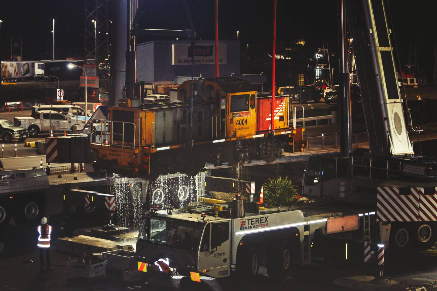 A KiwiRail shunt locomotive, which fell into Picton Harbour last week, was lifted out of the water by two cranes on Friday night. Photo / Jim Tannock