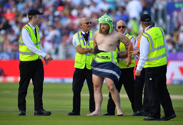 A streaker is taken from the ground in the World Cup game between England and New Zealand. Photo /Getty