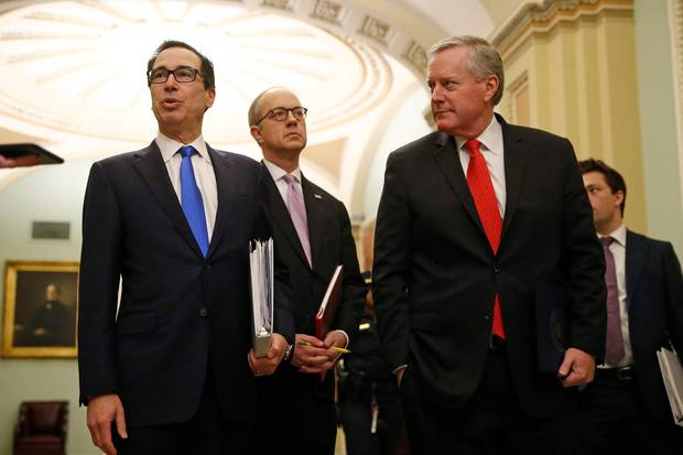 Treasury Secretary Steven Mnuchin, left, accompanied by White House Legislative Affairs Director Eric Ueland and acting White House chief of staff Mark Meadows, speaks with reporters. Photo / AP