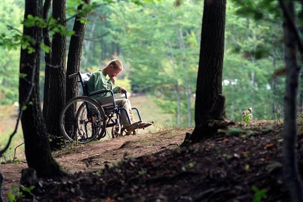 Një vajzë e re shqiptare e paralizuar ulet në karrigen me rrota në kampin e refugjatëve pyjor.  Foto / Përplas Goddard