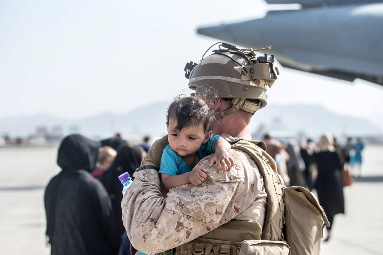 A US Marine calms an infant during an evacuation at Hamid Karzai International Airport in Kabul, Afghanistan. Photo / US Marine Corps via AP