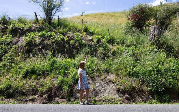 Pamela Coleman at the sight of the accident, pointing up to the area from where the tree stump tumbled onto her vehicle. Photo / RNZ / Nick Monro