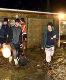 Henley farmer Josh Adam (carrying a gas cylinder) and his wife are helped with friends as they evacuate their low lying farm at 10.30pm. Photo / Otago Daily Times