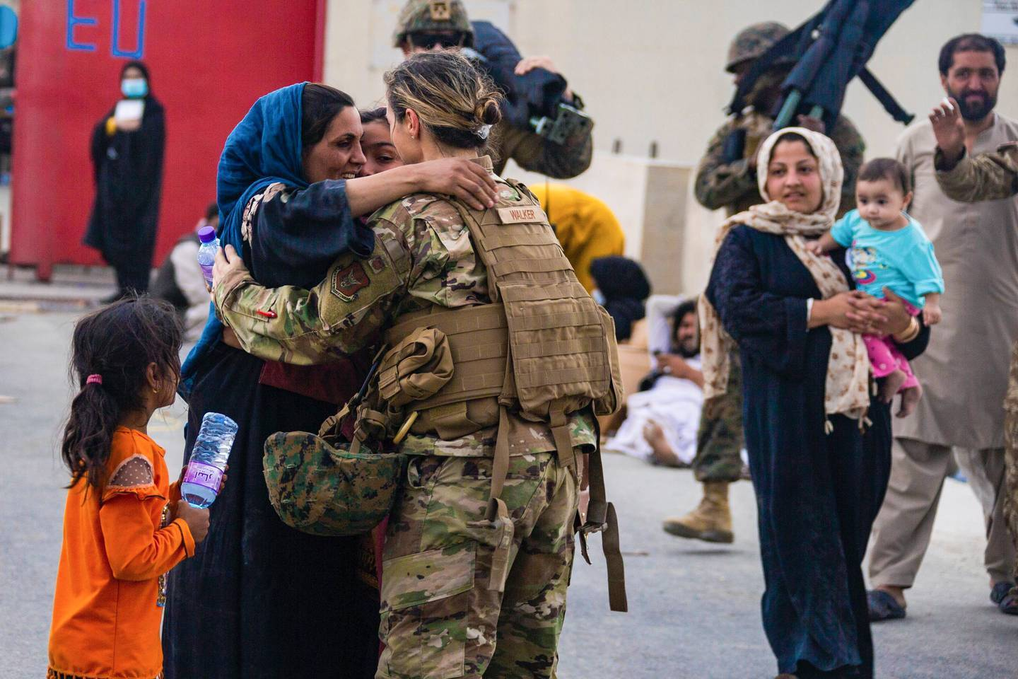 A US Airman with the Joint Task Force-Crisis Response embraces a mother after helping reunite their family at Hamid Karzai International Airport in Kabul. Photo / AP