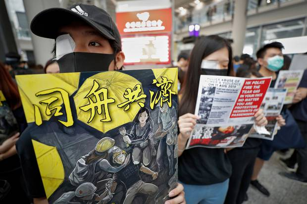 Protesters wear eyepatches during a protest at the arrival hall of the Hong Kong International Airport following reports that police shot a woman in the eye. Photo / AP