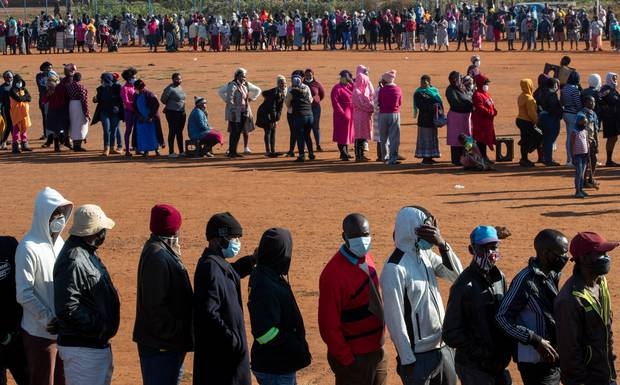 People affected by the coronavirus economic downturn line up to receive food parcels in Pretoria, South Africa. Photo / AP