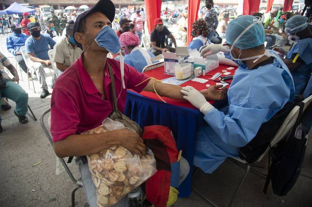 A health worker takes a blood sample for a quick COVID-19 test from man who works selling cookies at the Coche food market in Caracas, Venezuela. Photo / AP