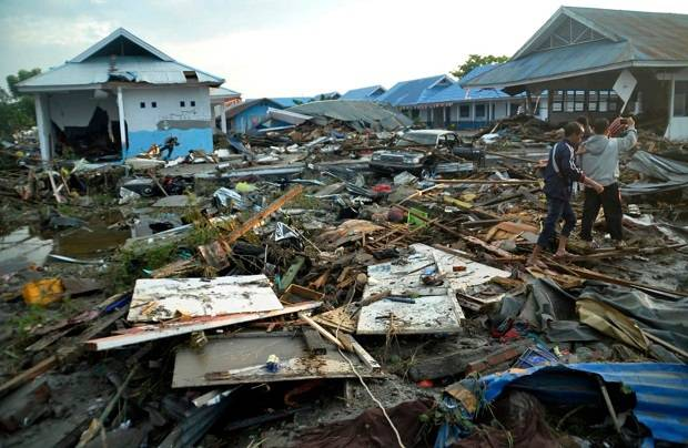 Indonesian men survey the damage following earthquakes and a tsunami in Palu, Central Sulawesi, Indonesia. Photo / AP