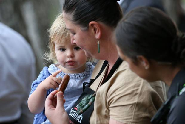 Local government MP Willow-Jean Prime gives the Prime Minister's daughter Neve a sausage from the barbecue cooked by her mother, PM Jacinda Ardern. Photo / Getty Images
