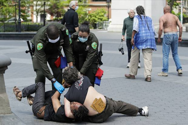 Police officers break up a fight during the coronavirus pandemic in Washington Square Park in New York. Photo / AP