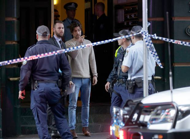 A witness assists police at a building where a woman's body was found after a man attempted to stab multiple people in Sydney. Photo / AP