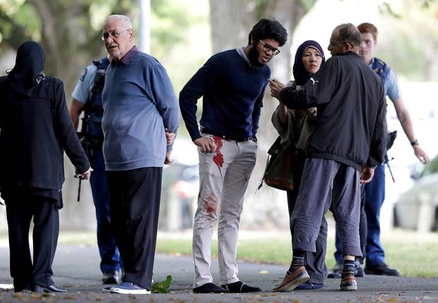 People stand across the road from a mosque in central Christchurch. Photo / AP
