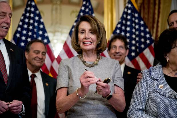 House Speaker Nancy Pelosi of Calif., accompanied by House Democratic members stand after signs a deal to reopen the government on Capitol Hill in Washington. Photo / AP