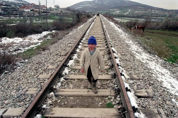 Një djalë i vogël ecën gjurmët hekurudhore ndërsa familja e tij ikën nga fshatrat e tyre.  Foto / Përplas Goddard