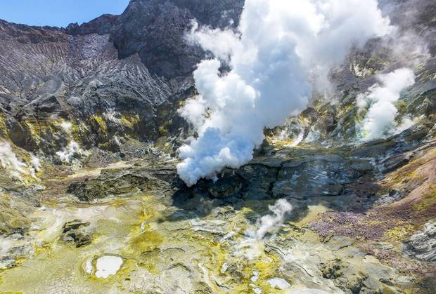 Beneath White Island's sheer walls of sulphur-yellow and iron-red, gas spews from the sides of hollow domes of rock, and hot streams bubble. Photo / Alan Gibson