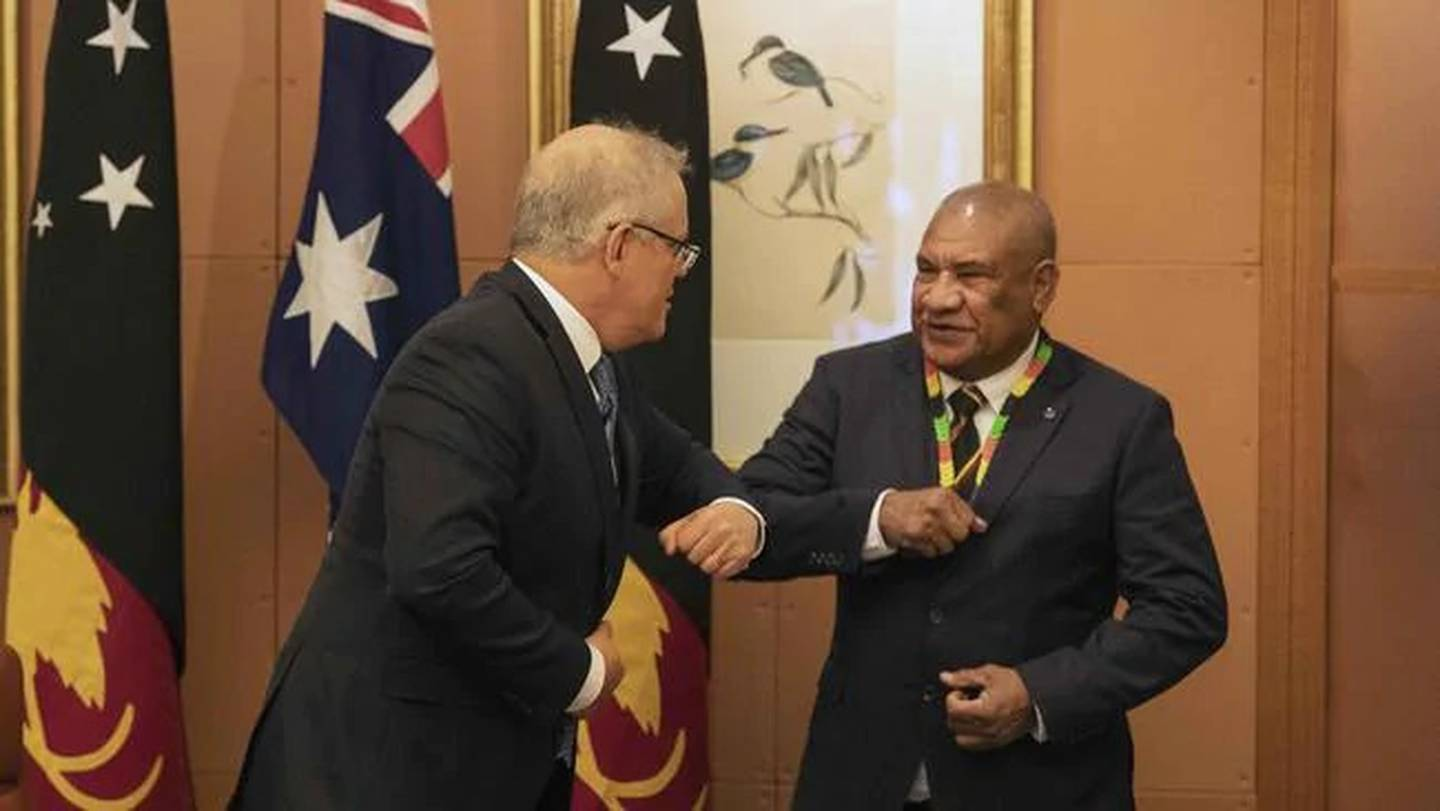 Prime Minister Scott Morrison shoulder bumps PNG's High Commissioner John Kali. PNG is in a tug of war between China and Australia. Photo / News Corp Australia