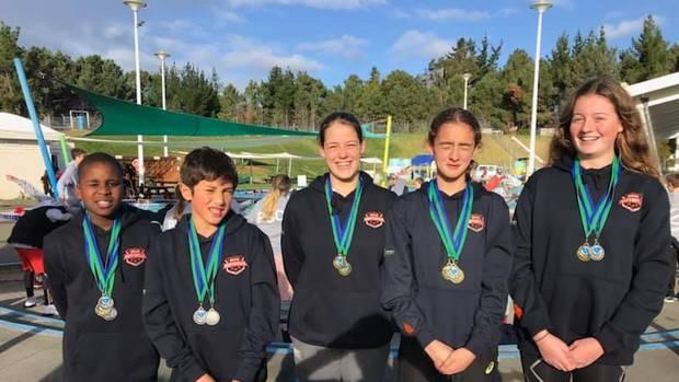 Swim Rotorua's Ariel Muchirahondo (left), Hone Curtis, Emily Spear, Kaia Joyce and Molly Sinclair were some of the medal winners at the Taupō Xlr8 swim meet. Photo / Supplied