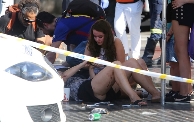 Injured people are treated in Barcelona after a white van jumped the sidewalk in the historic Las Ramblas district. Photo / AP