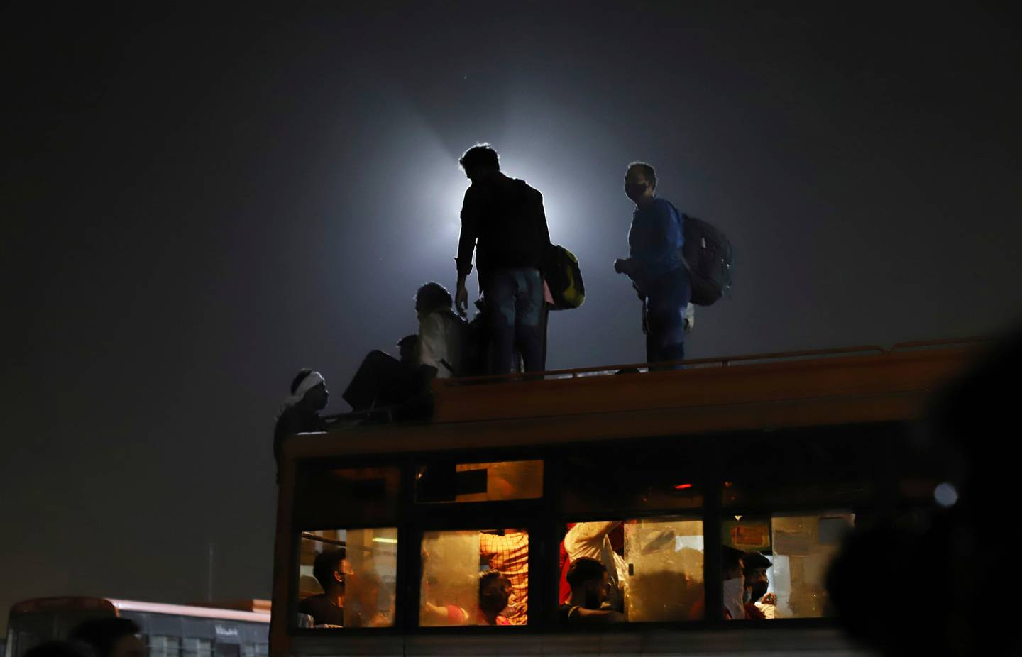 Migrant workers leave for their villages from a bus terminal, in New Delhi, India. Photo / AP