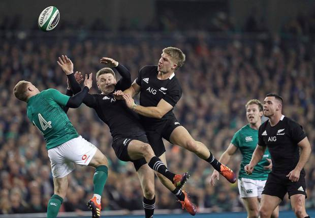 Ireland's Keith Earls, left, and New Zealand's Beauden Barrett, center, battle for a high ball during the rugby union international between Ireland and the New Zealand All Blacks. Photo / AP