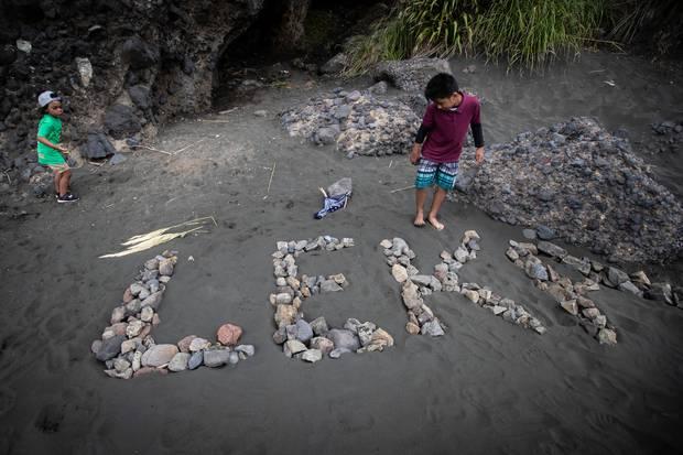 Saulala Jr Fononga, left, and Litani Jr Katoa write a tribute to their cousin Leka Pasiaka at the beach.