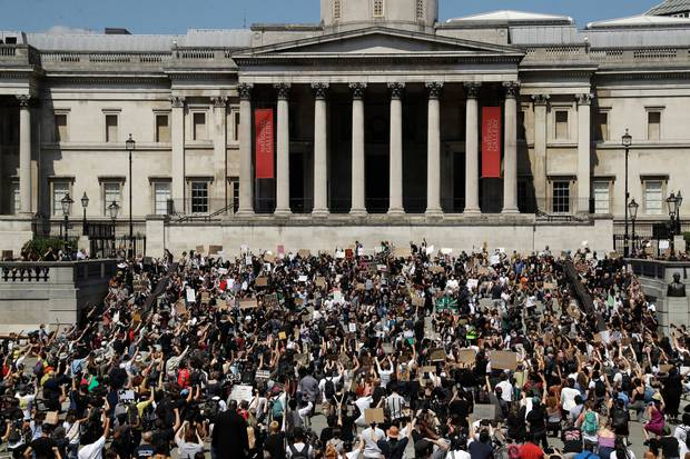 People, some of them kneeling, gather in Trafalgar Square in central London yesterday to protest against the killing of George Floyd by police officers in Minneapolis. Photo / AP
