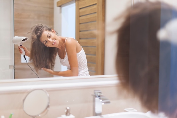 While drying your hair upside down does give it volume, the best thing is to get the nozzle of the dryer as close to the scalp as possible to get lift. Photo / Getty Images