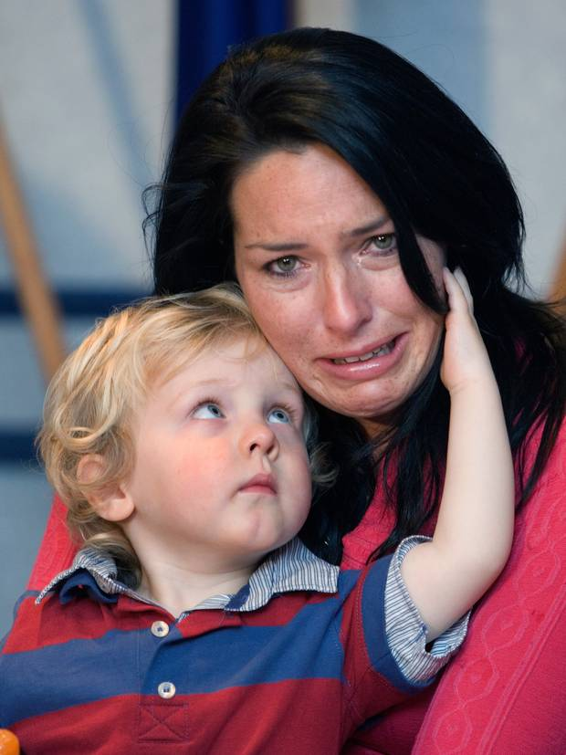 Kylee Guy, wife of murdered Feilding farmer Scott Guy, is comforted by her two-year-old son, Hunter, during an emotional 2010 press conference in Palmerston North following the murder. Photo / File