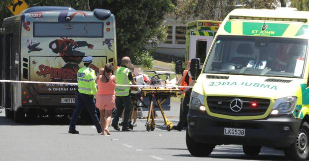 A injured person is assisted by ambulance staff and police at the scene of the crash. Photo / Michael Craig
