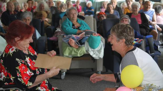 Jackie Simkins about to receive a gift from resident Julia Clarke. Picture / Peter Jackson