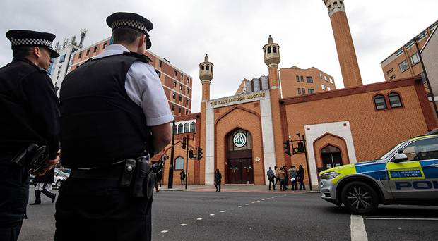 Police officers stand on patrol outside the East London Mosque. Photo / Getty