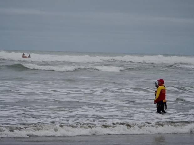 Bethells Beach surf lifesaving crewmen hit the water to help find the fisherman. Photo / SLNZ