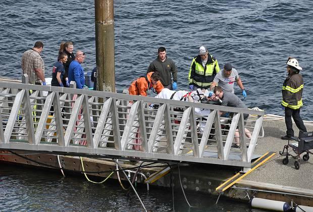 Emergency response crews transport an injured passenger to an ambulance at the George Inlet Lodge docks. Photo / AP