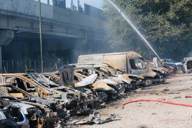 A firefighter sprays water among charred vehicles under the highway.