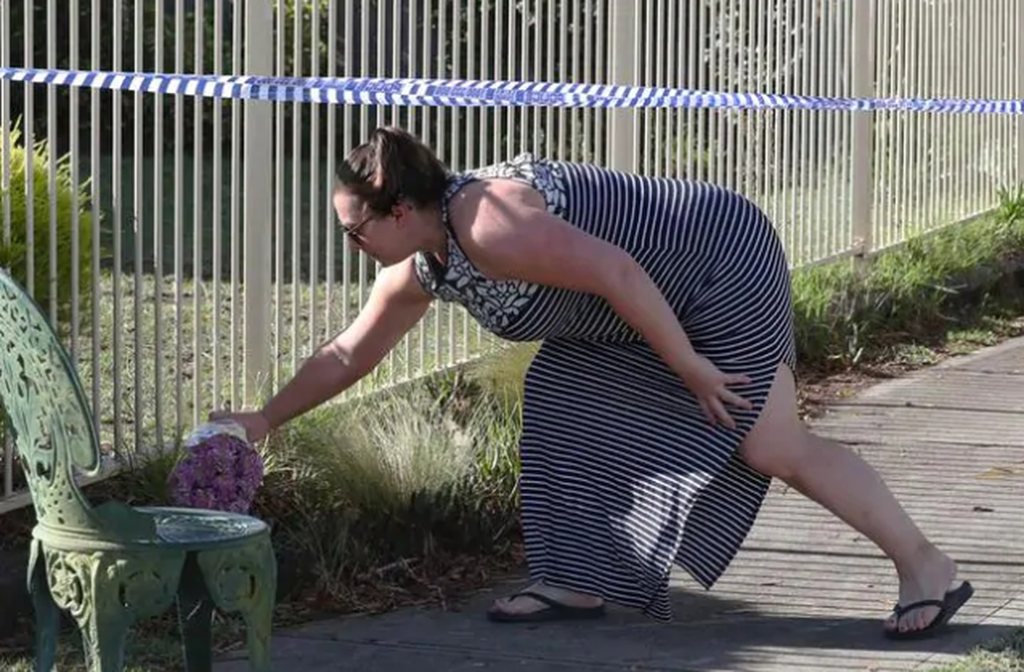 A woman leaves flowers outside the Perinovic home. Photo / NCA NewsWire