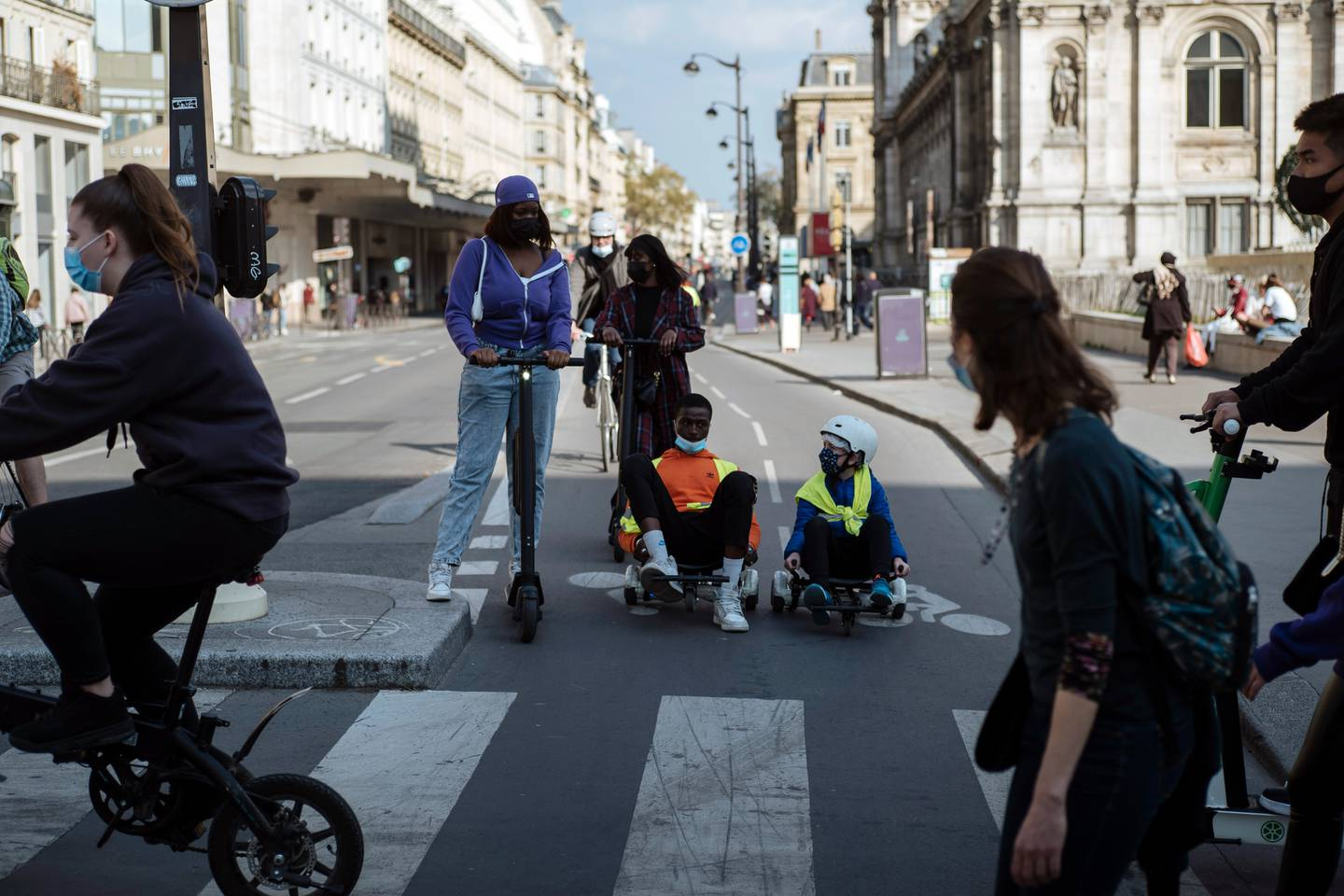People, wearing face masks to prevent the spread of the coronavirus, ride electric scooters, in Paris. Photo / AP
